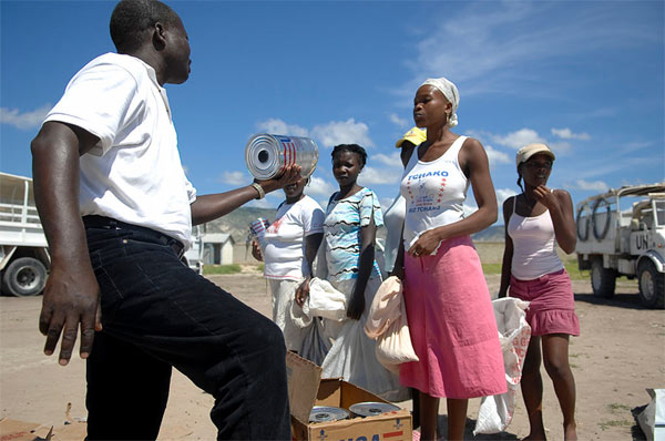 Haitian families receive goods from U.N. officials during relief efforts after hurricane in 2008