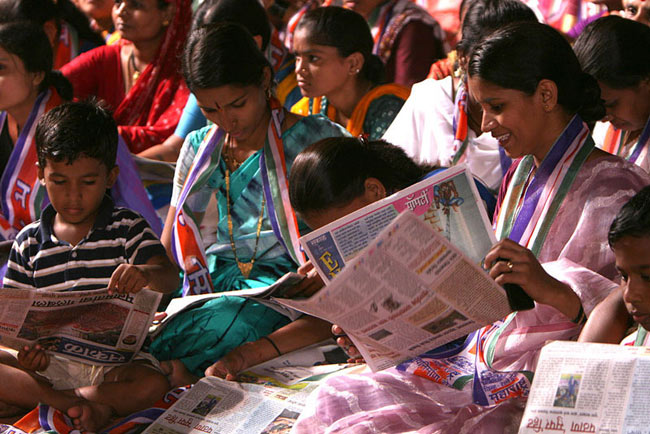 Indian voters read regional newspapers at a rally in Mumbai